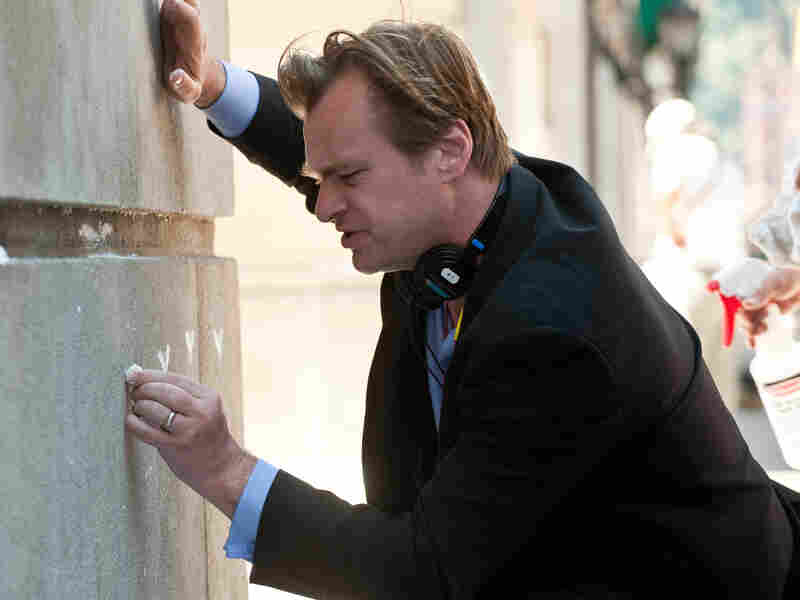 Christopher Nolan on the set of The Dark Knight Rises, drawing some Batman graffiti.