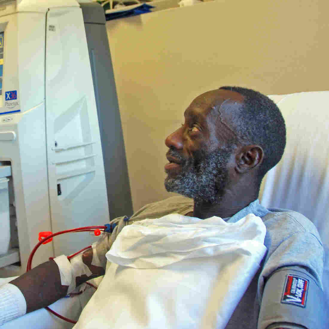 While Kenya Jackson (right) is on his thrice-weekly dialysis treatment, community health worker Greg Jules talks to him about taking his medication.