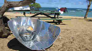 Corn dogs sizzle in a solar cooker made from reflective car windshield shades.