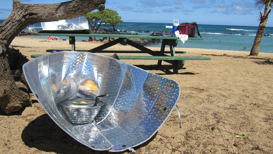 Corn dogs sizzle in a solar cooker made from reflective car windshield shades. (Flickr)
