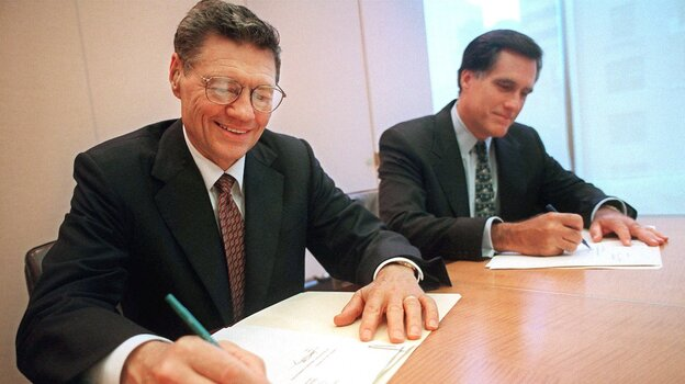 """Thomas Monaghan (left), founder and chairman of Domino's Pizza, signs an agreement to sell a """"significant portion"""" of his stake in the company to Mitt Romney's Bain Capital, in 1998. Romney, then Bain's CEO, maintains that he left the firm the following year."""