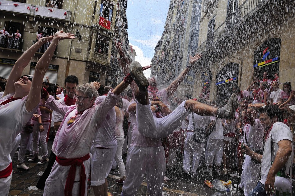 "Water is thrown from a balcony during the ""Chupinazo,"" the official opening of the San Fermin fiesta on July 6. (AP)"