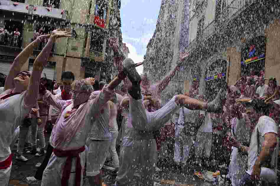 "Water is thrown from a balcony during the ""Chupinazo,"" the official opening of the San Fermin fiesta on July 6."