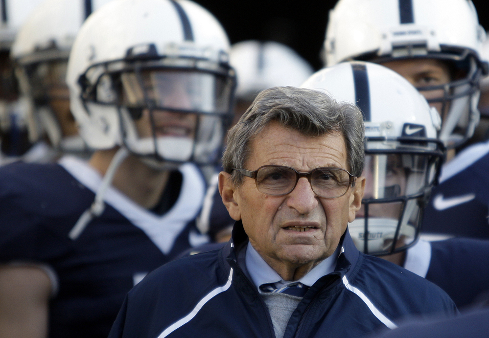 Former Penn State Coach Joe Paterno stands with his players in 2009.
