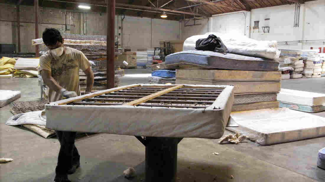 A worker dismantles a mattress at a recycling facility in Oakland, Calif. The material will be used to make carpet products and proceeds will help support the St. Vincent de Paul Society of Lane