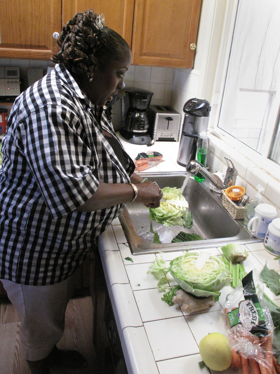 Yovanda Dixon washes vegetables in her San Francisco home to prepare a demonstration for her support group. (NPR)