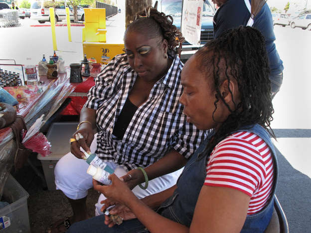 Yovanda Dixon (left) shows fellow group member Pamela Travis some of the bath oils she sells outside a San Francisco grocery store as part of her business Scentuality.