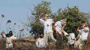 Jewish settlers in the West Bank throw stones during clashes with Palestinians near the city of Nablus on May 19. A new report says violence by settlers directed at West Bank Palestinians is up sharply over the past three years.