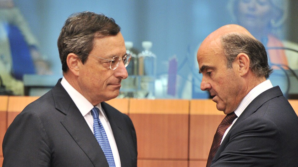 European Central Bank president Mario Draghi, left, speaks with Spanish Finance Minister Luis De Guindos on Monday. The ECB has increased its influence over European countries struggling with debt. (AFP/Getty Images)