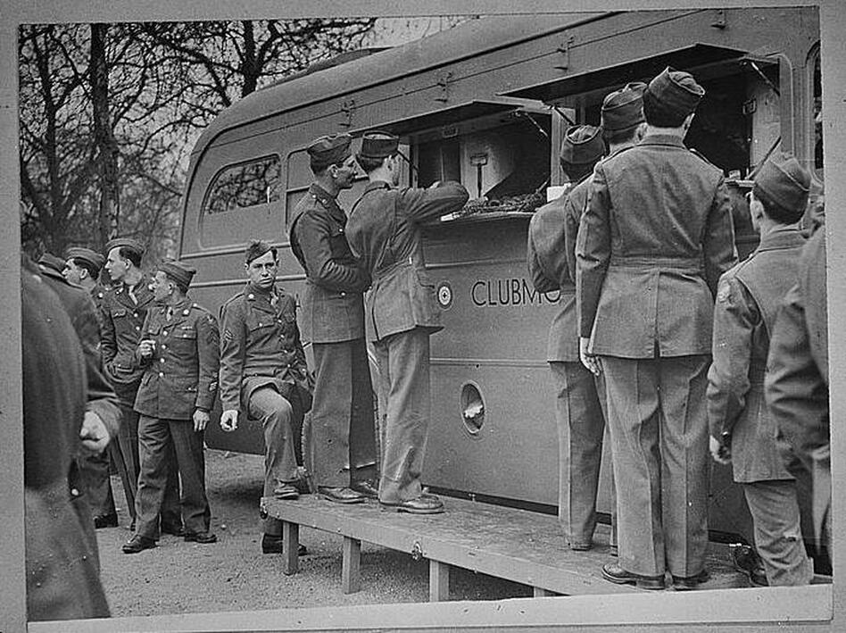 U.S. soldiers receive refreshments, including doughnuts, from an American Red Cross clubmobile in London. Soldiers today still resent a Red Cross move to charge for doughnuts. (Library of Congress)