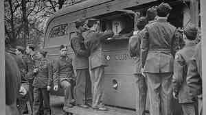 U.S. soldiers receive refreshments, including doughnuts, from an American Red Cross clubmobile in London. Soldiers today still resent a Red Cross move to charge for doughnuts.