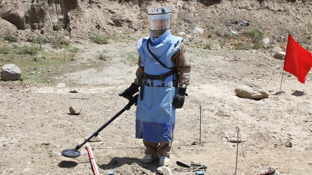 A de-mining expert demonstrates how to find land mines in a training area near Hakim Village in central Afghanistan, where Soviet mines dating to the 1980s are