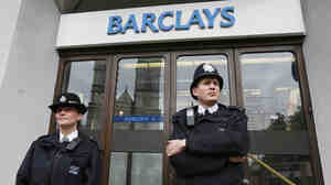 Police wait for protesters to appear at a branch of Barclays Bank in London on July 4.