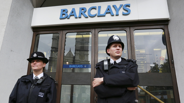 Police wait for protesters to appear at a branch of Barclays Bank in London on July 4. (Reuters/Landov)