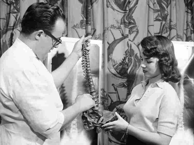 Lois Conway stands by her spinal X-ray and reviews a model of the human spine with a chiropractor.
