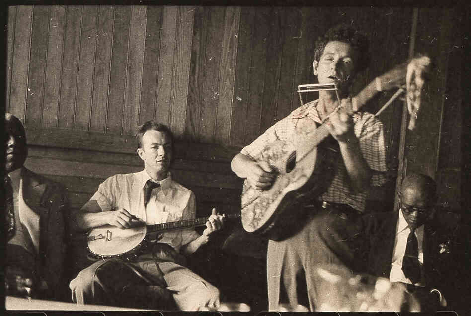 "Guthrie plays his signature guitar with ""This machine kills fascists"" scrawled across the front. Pete Seeger accompanies on banjo; music journalist Dan Burley sits at left."