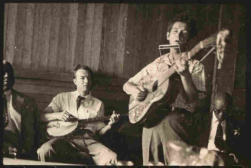 """Guthrie plays his signature guitar with """"This machine kills fascists"""" scrawled across the front. Pete Seeger accompanies on banjo; music journalist Dan Burley sits at left."""