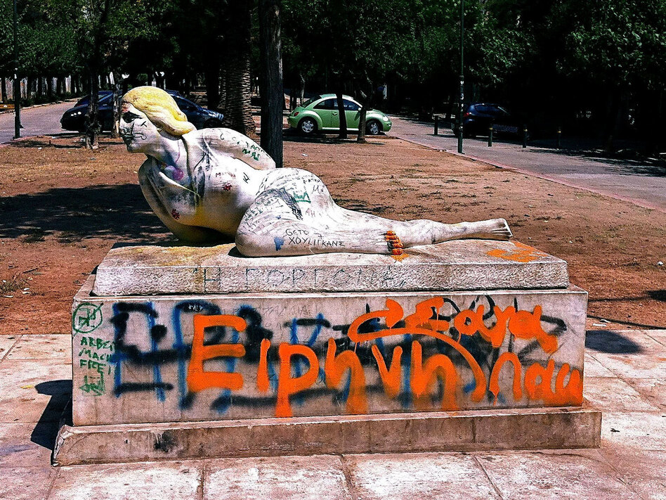 Graffiti coats a statue near the National Archaeological Museum in Athens. The street is often filled with drug users at night.