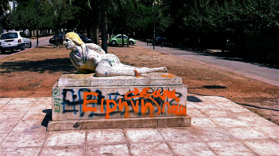 Graffiti coats a statue near the National Archaeological Museum in Athens. The street is often filled with drug users at night. (NPR)