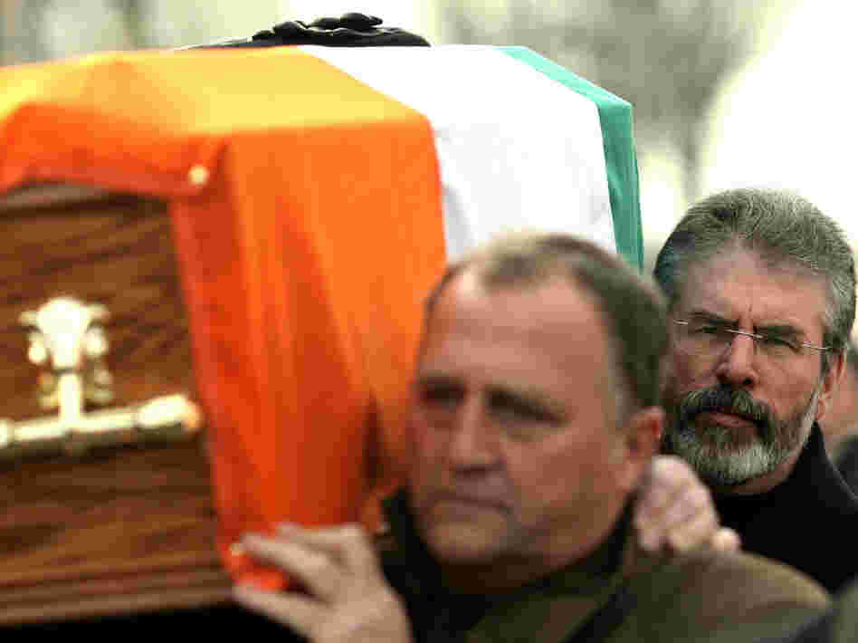 Sinn Fein President Gerry Adams, right, carries the coffin of senior IRA commander Brendan Hughes, in West Belfast, Northern Ireland.
