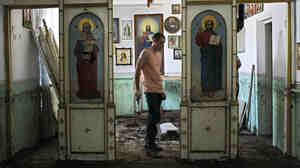 An Emergency Ministry soldier helps to repair religious icons in a church hit by flood water in the town of Nizhnebakansky, about 750 miles south of Moscow, on Tuesday.
