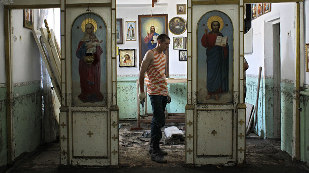 An Emergency Ministry soldier helps to repair religious icons in a church hit by flood water in the town of Nizhnebakansky, about 750 miles south of Moscow, on Tuesday. (AP)