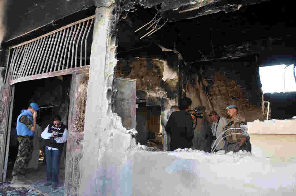UN observers inspect a bombed-out school in the Syrian village of Tremsah, where as many as 200 people may have been killed after an armed conflict erupted last week.