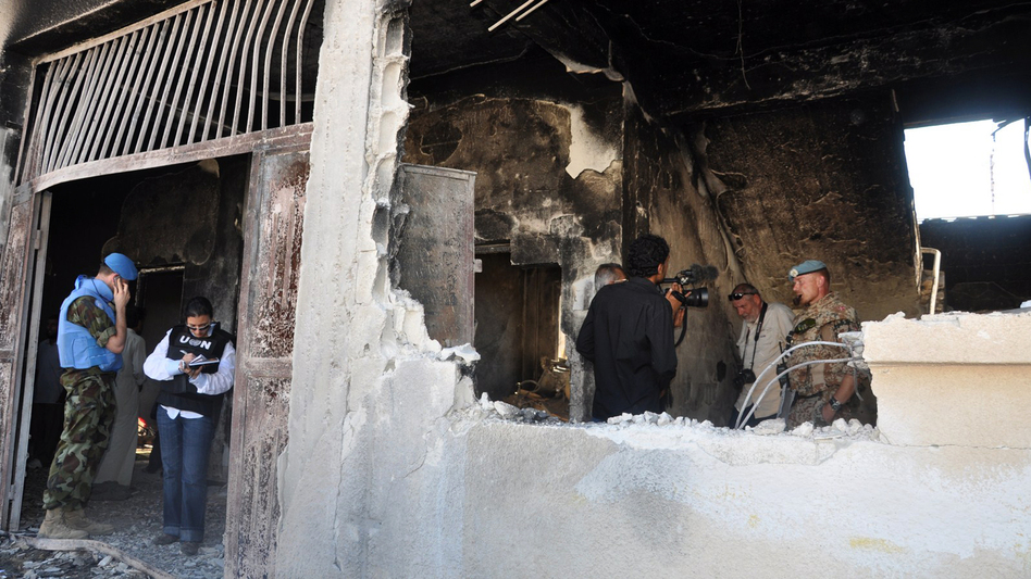 UN observers inspect a bombed-out school in the Syrian village of Tremsah, where as many as 200 people may have been killed after an armed conflict erupted last week. (AFP/Getty Images)