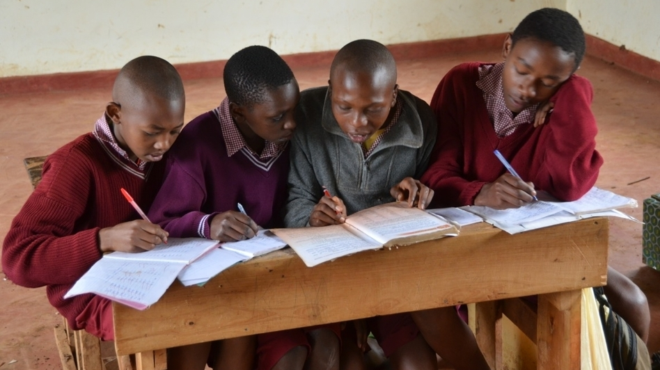 Kenya has made its public schools free, which has dramatically increased the number of students. But this has also led to overcrowding. Here, four boys share a desk and a single textbook at the Amboni Secondary School in central Kenya. (Courtesy of Turk Pipkin)