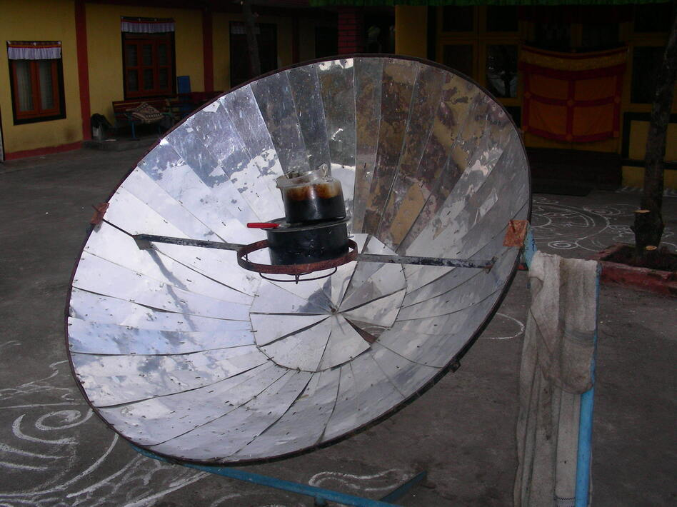 A parabolic solar cooker heats up a tea kettle in Nepal. (Flickr)