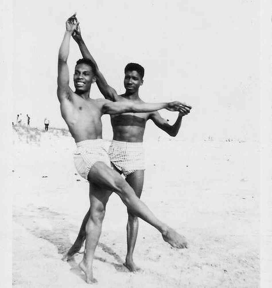 Two men dance on the beach.