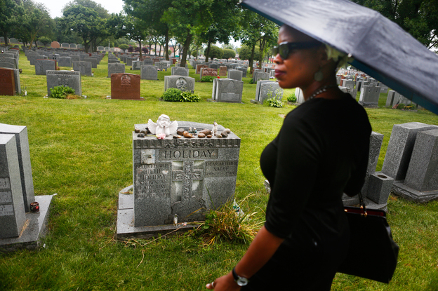 Queen Esther stands in front of Billie Holiday's gravesite in New York City.