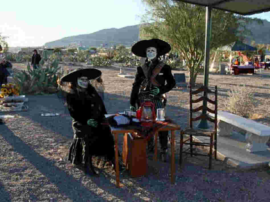 A couple celebrates Dia de los Muertos at the Concordia Cemetery.