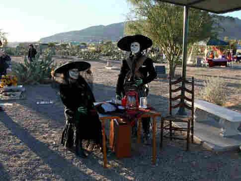A couple celebrates Dia de los Muertos at the Concordia Cemetery.