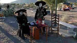 A couple celebrates Dia de los Muertos at the Concordia Cemetery in El Paso, Texas.