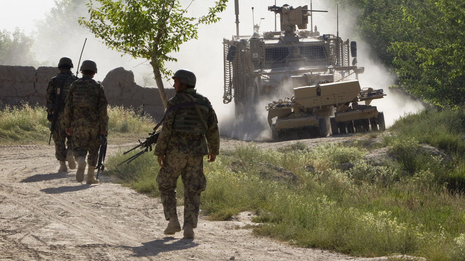 Afghan soldiers walk toward a U.S. Army mine-sweeping vehicle in southern Afghanistan on June 10. Roadside bombs remain a major threat to U.S. and Afghan troops, as well as civilians. (Reuters /Landov)