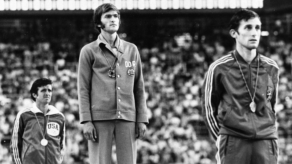 Marathon medal winners listen to the anthem from the victory stand during the presentation ceremony at the XXI Summer Olympic Games in Montreal in 1976. From left, Frank Shorter, U.S.A., silver; Waldemar Cierpinski, East Germany, gold, Olympic record; and Karel Lismont, Belgium, bronze. Evidence of doping by the East Germans suggests that Shorter deserved the gold medal. (AP)