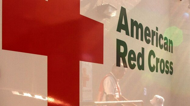 Red Cross volunteers are reflected in an emergency-response vehicle as they stock supplies in Colorado Springs, Colo., in early July, ahead of visiting neighborhoods affected by the Waldo Canyon wildfire.