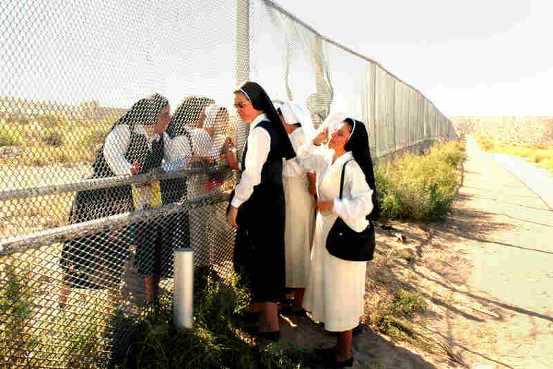 Sisters at the Border, 2007. Nuns meet at the border of Anapra, N.M. (left), and Barrio Anapra, Juarez. The nuns in Mexico cannot cross for various reasons — except on the day of a Mass for immigrants, held every November in the U.S.