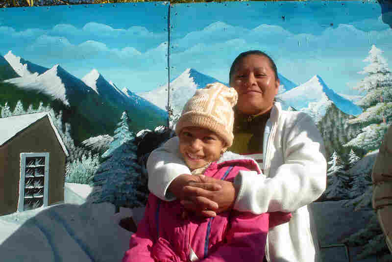 Las Sierras de Juarez, 2006. A mother and daughter in the Plaza de Juarez in front of a photographer's backdrop.