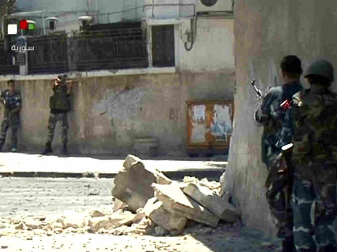Video taken from Syrian TV purportedly shows government forces taking up position during clashes with rebels Wednesday in the Al-Midan district of Damascus.