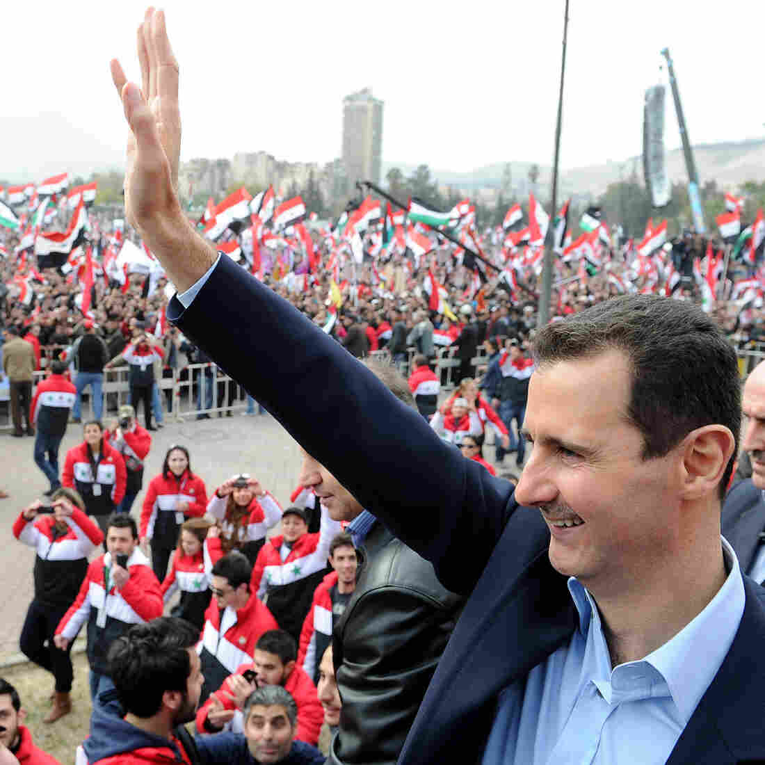 Syrian President Bashar Assad waves at supporters during a rare public appearance in Damascus on Jan. 11.