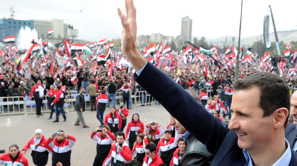 Syrian President Bashar Assad waves at supporters during a rare public appearance in Damascus on Jan. 11. (AFP/Getty Images)
