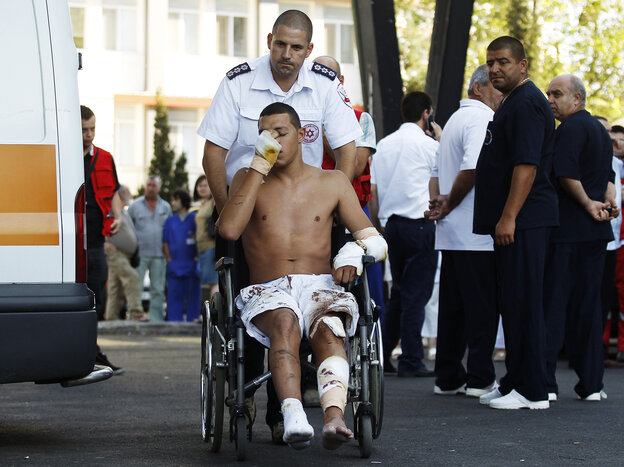 An Israeli survivor is carried on a wheelchair to an ambulance as he leaves a hospital in Burgas, Bulgaria, on T