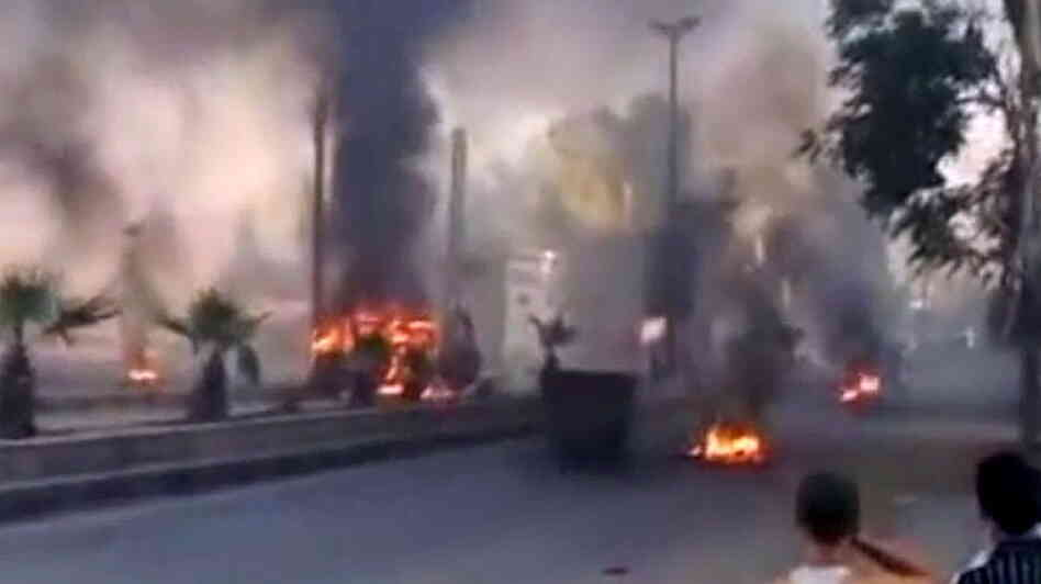 An image grab taken from a video uploaded on YouTube on Wednesday shows smoke billowing from burning tires and trash containers in Damascus.