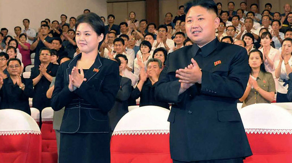 In this photo released by the Korean Central News Agency and distributed in Tokyo by the Korea News Service on July 9, North Korean leader Kim Jong Un is seen with a woman in Pyongyang. It's not clear who she is, but a first lady would be a marked departure from the days of Kim's father, who kept his personal life private. (AP)