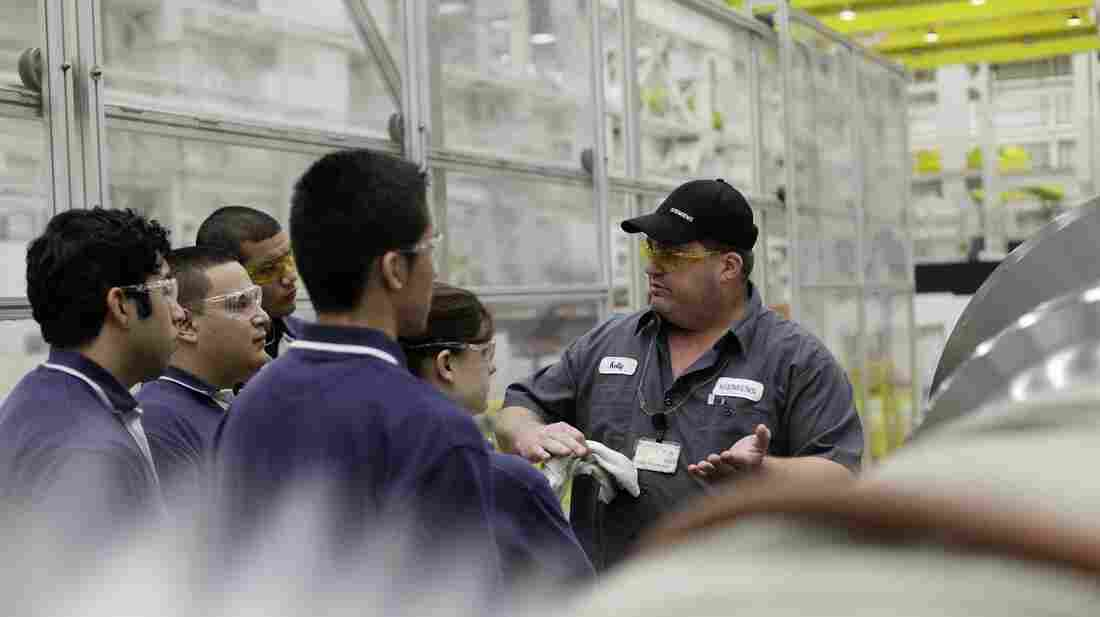 Kelly Thompson, a mentor at Siemens, gives apprentices an orientation of the factory. The program provides on-the-job training in manufacturing.