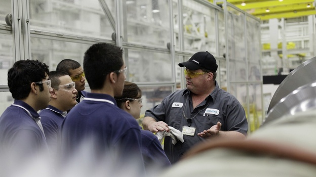 Kelly Thompson, a mentor at Siemens, gives apprentices an orientation of the factory. The program provides on-the-job training in manufacturing. (Courtesy of Siemens Energy Inc.)