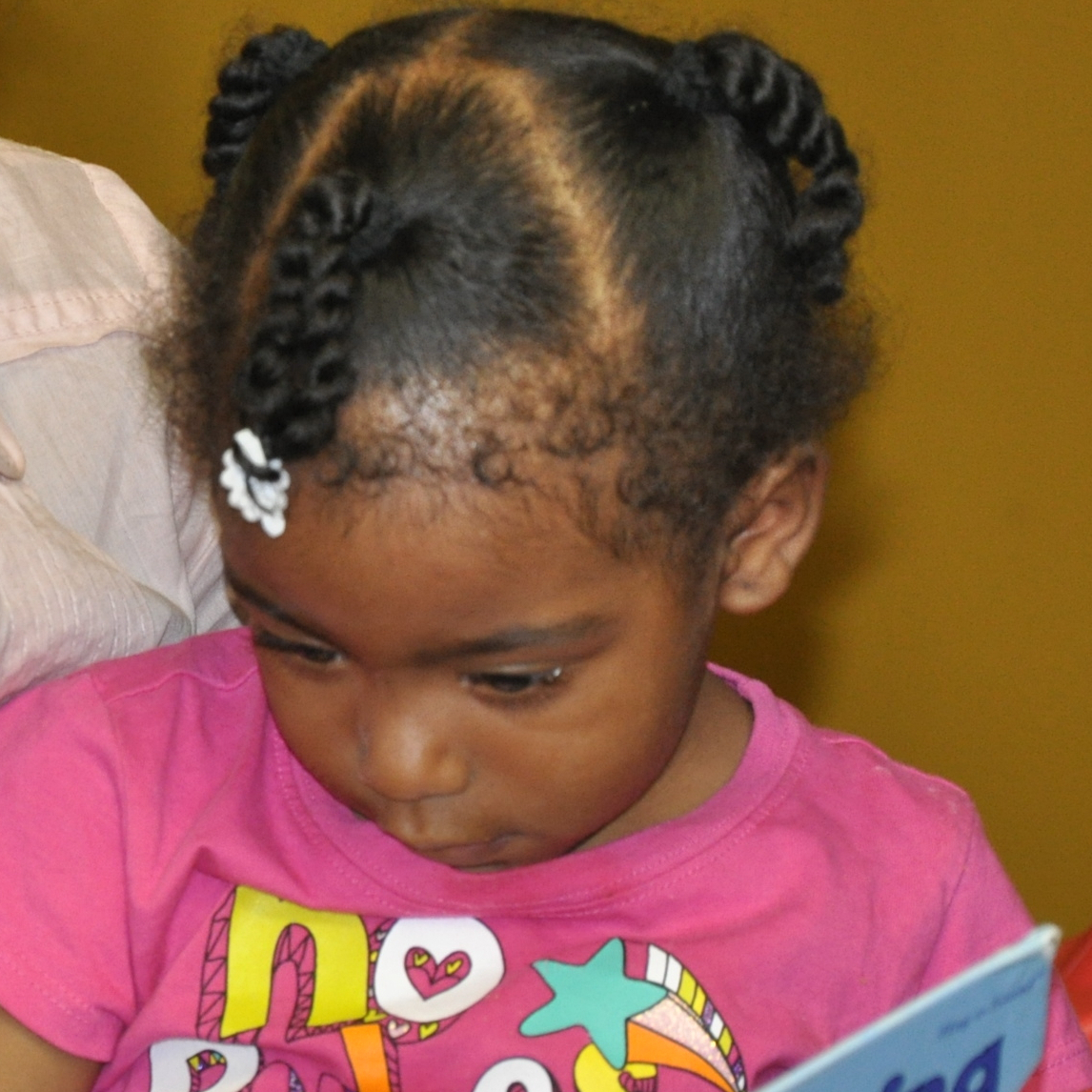 A volunteer reads a book with a visitor at The Homeless Children's Playtime Project.
