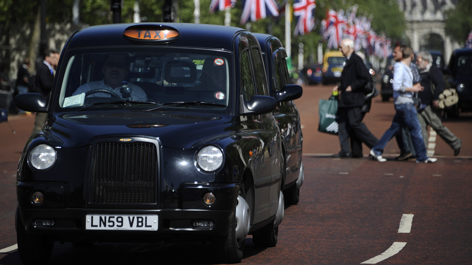 Black taxis drive through London. Weekend Edition knows one London cabbie who treats reading like an Olympic sport. (AFP/Getty Images)